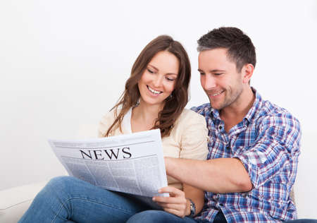 Portrait Of A Happy Young Couple Sitting On Couch Reading Newspaper