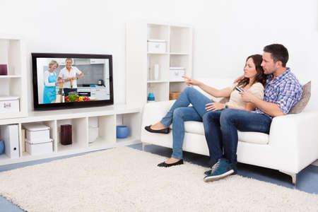 pareja viendo tv: Pareja joven sentado en el sof� que ve la Cocina Mostrar Foto de archivo