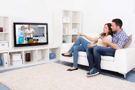 woman watching tv: Young Couple Sitting On Couch Watching Cookery Show