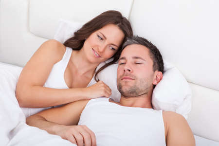 Happy Young Woman Looking At Man Sleeping photo