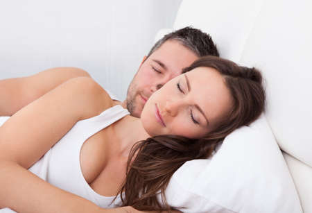 beard woman: Young Couple Sleeping Side By Side On Bed Stock Photo