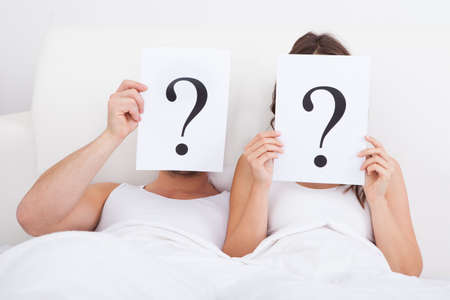 quizzical: Couple Lying On Bed Holding Question Mark On Face