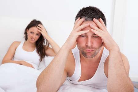 pareja en la cama: Hombre frustrado Sentado en la cama delante de la mujer joven