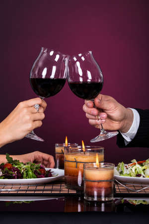 romantic evening with wine: Smiling Couple Tossing Wine Glass While Having Dinner