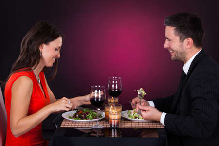 Happy Man Holding Fork Looking At Woman Eating Food photo