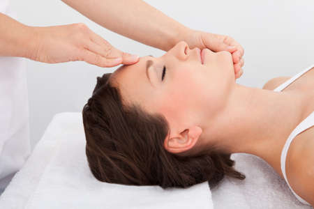 Young Woman With Eyes Closed Getting Massage Treatment From Masseuse Stock Photo - 24284844