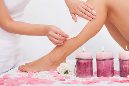 rejuvenate: Beautician Waxing A Womans Leg Applying Wax Strip
