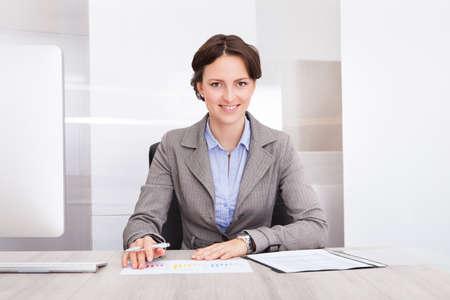 revisando documentos: Retrato de una sonriente joven empresaria sentada en escritorio Foto de archivo