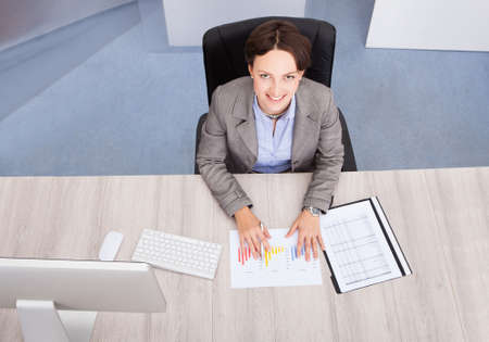 High Angle View Of Businesswoman Smiling Young Businesswoman At Desk photo