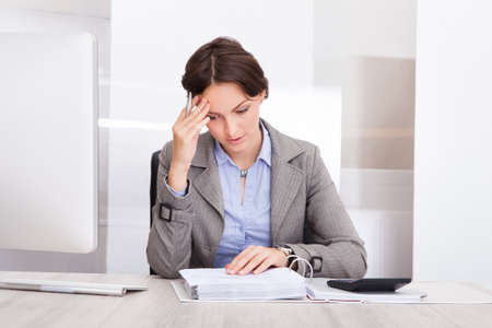 contemplated: Portrait Of A Contemplated Businesswoman Calculating Bills