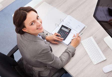 Retrato de sonriente joven mujer contable calcular facturas