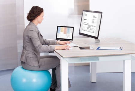 Young Businesswoman Sitting On Pilates Ball Using Computer In Office