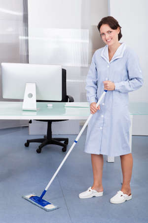 cleaning an office: Portrait Of Happy Female Janitor Cleaning Floor At Office
