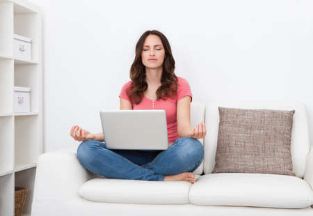 Portrait Of A Young Woman With Laptop Practicing Yoga Sitting On Couch