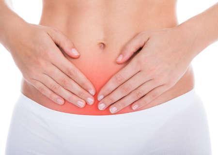 menstruacion: Mujer joven con dolor en su estómago Aislado Sobre Fondo Blanco Foto de archivo