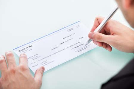 青年実業家のオフィスの机で空白の小切手を充填