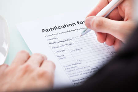Close-up Of Mans Hand Filling Application For Employment photo