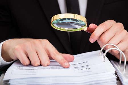 zvětšovací: Podnikatel při pohledu na dokument skrz zvětšovací sklo