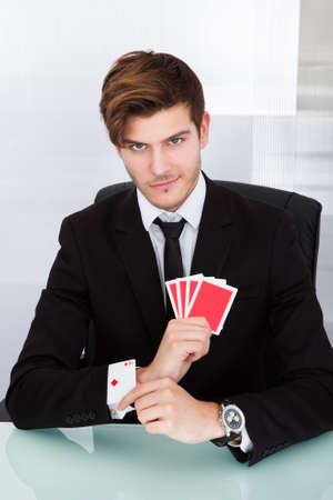 advantages: Portrait Of A Young Businessman With Playing Cards In Sleeve