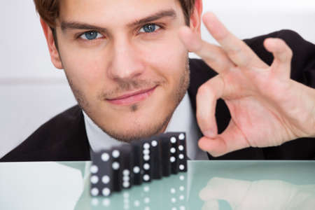 Young Businessman Playing Domino At Office Desk photo