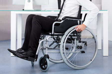 wheelchair man: Close-up Of Businessman Sitting On Wheelchair In Office Stock Photo