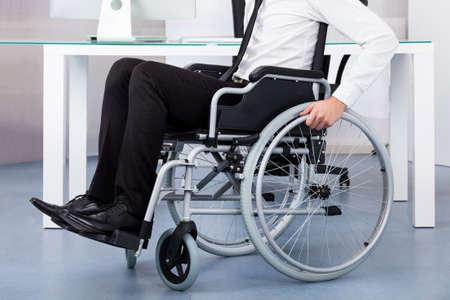 lesionado: Primer Plano De negocios sentado en silla de ruedas En Office