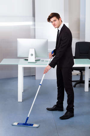 Portrait Of A Young Businessman Cleaning Office With Mop Stock Photo