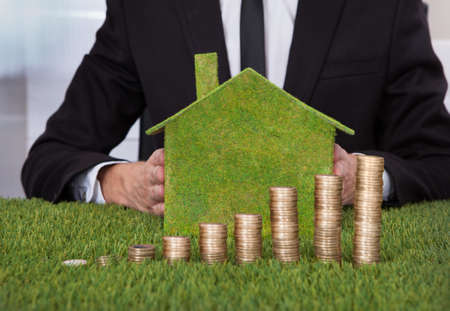 Businessman Holding Eco Friendly House In Front Of Stack Of Coins Over Grass photo
