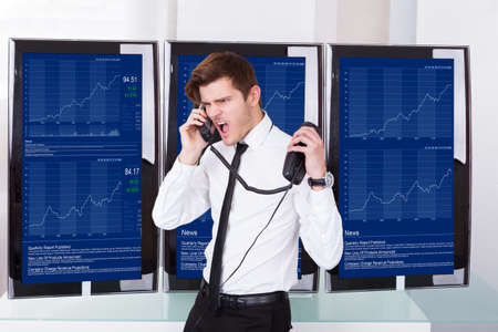 Furious Young Stock Broker Talking On Telephone In Front Of Computer Screen
