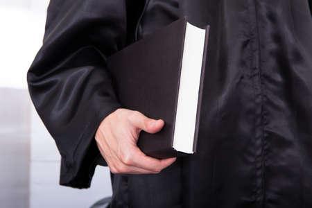 法律の本を持ってローブの男性判事のクローズ アップ