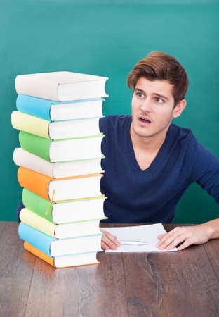 Portrait Of A Shocked Male Student Looking At Stack Of Books photo
