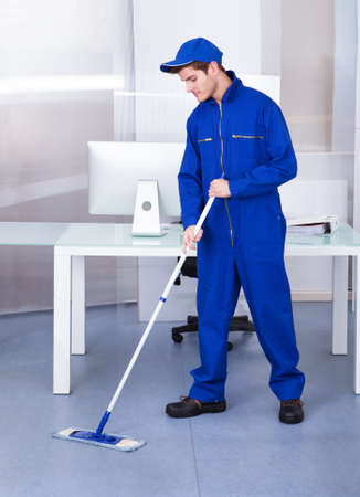 Portrait Of A Male Worker Cleaning Floor With Mop photo