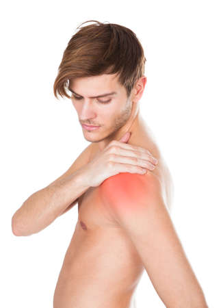 Shirtless Young Man Suffering From Shoulder Pain On White Background photo