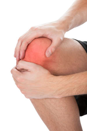 on hands and knees: Close-up Of Man Suffering From Knee Injury On White Background Stock Photo