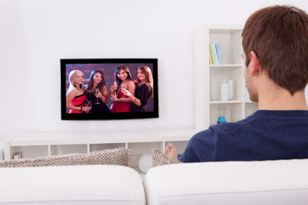 woman watching tv: Rear View Of Man Watching Television At Home Stock Photo