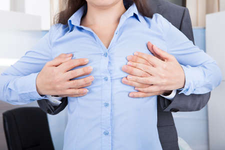 Close-up Of Businessman Touching Businesswoman's Breast In Office photo
