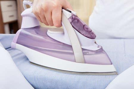 Close-up Van De Vrouw Hand strijken van kleding op de strijkplank