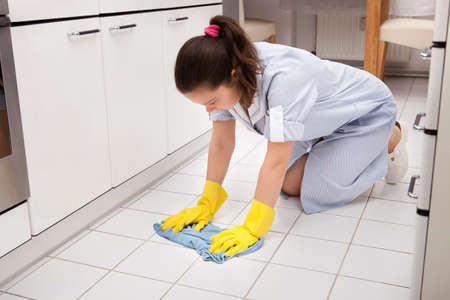Portrait Of Young Maid Wearing Gloves Cleaning Floor photo