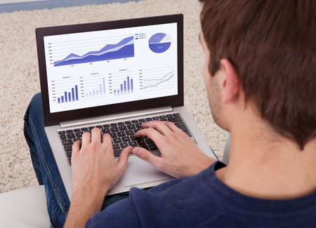 High Angle View Of Man Analyzing Graph On Laptop Stock Photo - 24285651