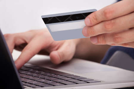 Person Holding Credit Card And Shopping Online Using Laptop photo