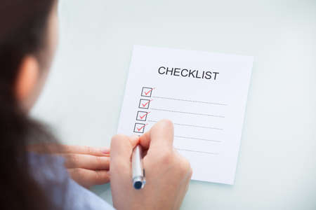 High Angle View Of A Businesswoman Marking On Checklist At Desk photo