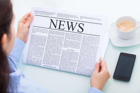 Veduta dall'alto di una imprenditrice leggendo il giornale con il cellulare al banco Archivio Fotografico - 24285657