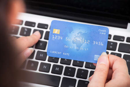 online trading: Close-up Of A Person Holding Credit Card Using Laptop