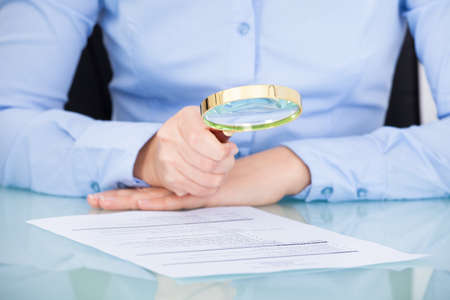 Businesswoman Looking At Document Through Magnifying Glass Stock Photo