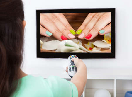 Close-up Of A Woman Holding Remote Control Changing Television Channel