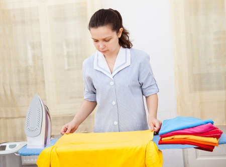 Portrait Of A Young Woman Ironing On Ironing Board photo