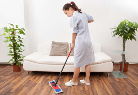 Portrait Of A Young Maid In Uniform Cleaning Floor With Mop photo