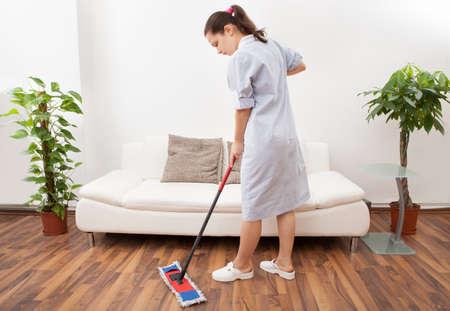 mujer limpiando: Retrato de una criada joven en la limpieza del piso uniforme con la fregona
