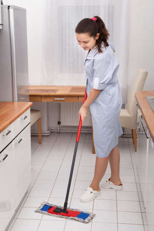 Portrait Of Young Maid In Uniform Cleaning Kitchen Floor photo