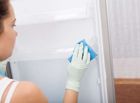 handglove: Rear View Of A Young Woman Cleaning Refrigerator Stock Photo